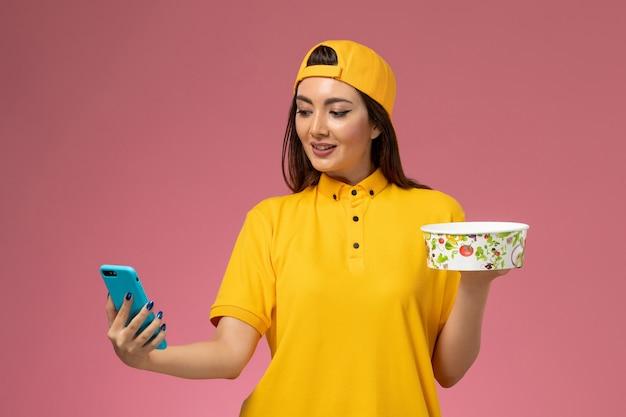 Вид спереди женщина-курьер в желтой форме и накидке, держащая миску для доставки и использующая телефон на светло-розовом столе, служба доставки униформы компании, работа, работа