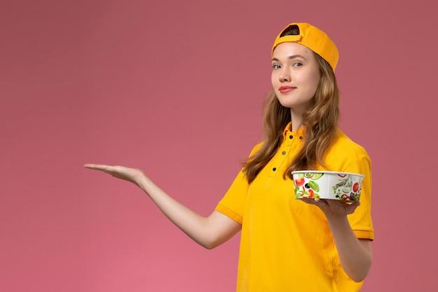노란색 유니폼과 케이프 핑크 벽 서비스 배달 작업 유니폼 작업자 소녀에 배달 그릇을 들고 전면보기 여성 택배