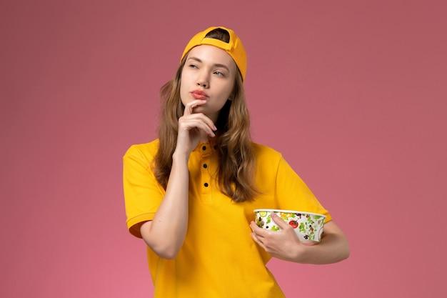Вид спереди женщина-курьер в желтой униформе и плаще, держащая миску для доставки, думающая о розовой стене, униформа службы доставки, работа компании