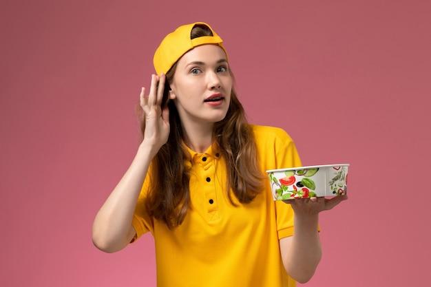 노란색 유니폼과 케이프 핑크 벽 서비스 배달 작업 제복 노동자 소녀에 들으려고 배달 그릇을 들고 전면보기 여성 택배