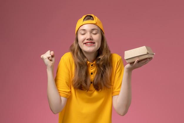 Вид спереди женщина-курьер в желтой форме и накидке, держащая посылку с доставкой на розовой стене, служба доставки, униформа, работа