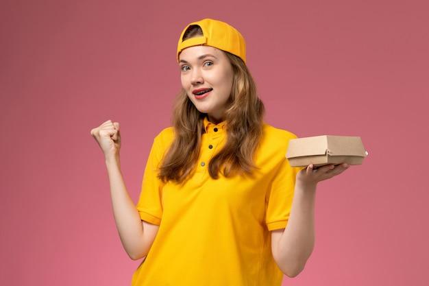 ピンクの壁のサービス配達制服の仕事で配達食品パッケージを保持している黄色の制服と岬の正面図の女性の宅配便