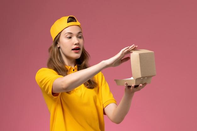 밝은 분홍색 벽 서비스 배달 유니폼 작업에 빈 작은 배달 음식 패키지를 들고 노란색 유니폼과 케이프에 전면보기 여성 택배