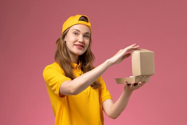 Вид спереди женщина-курьер в желтой форме и плаще с пустым маленьким пакетом еды для доставки на светло-розовой стене