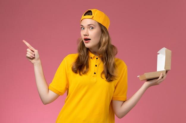 Вид спереди курьер-женщина в желтой форме и плаще с пустым маленьким пакетом еды для доставки на светло-розовой стене