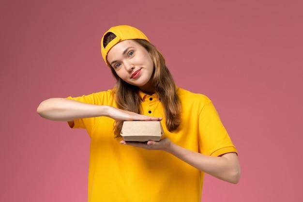 黄色の制服と薄ピンクの壁のサービス配達制服に空の小さな配達食品パッケージを保持している岬の正面図の女性の宅配便