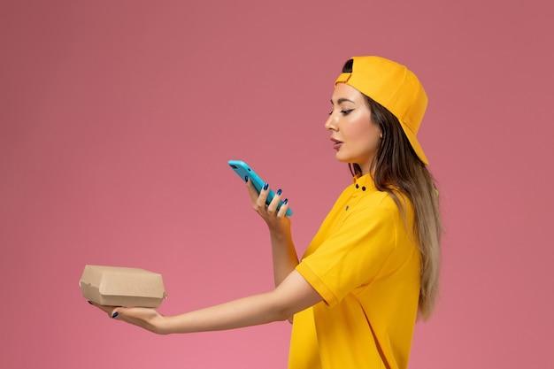 Курьер-женщина в желтой униформе и плаще, вид спереди, держит пакет с едой и фотографирует его на светло-розовой стене.