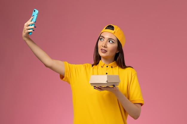 Вид спереди женщина-курьер в желтой униформе и накидке держит пакет с едой и фотографирует на светло-розовой стене доставка униформы компании