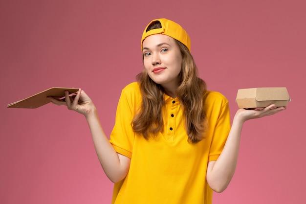 Вид спереди женщина-курьер в желтой форме и накидке с маленьким пакетом еды для доставки и блокнотом на светло-розовой стене работник службы доставки