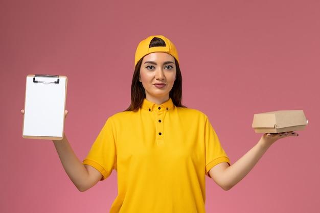 黄色の制服とケープの正面図の女性の宅配便は、淡いピンクの壁に小さな配達食品パッケージとメモ帳を保持していますサービス制服配達の仕事
