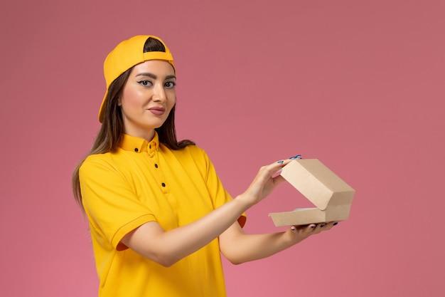 Вид спереди женщина-курьер в желтой униформе и плаще, держащая небольшой пакет продуктов для доставки и открывающая его на розовой стене, работа компании по доставке униформы