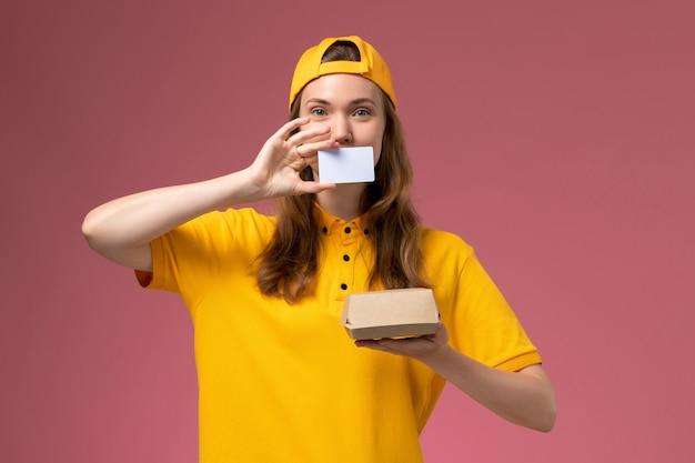 ピンクの壁の仕事サービス配達労働者に小さな配達食品パッケージとプラスチックカードを保持している黄色の制服と岬の正面図の女性の宅配便