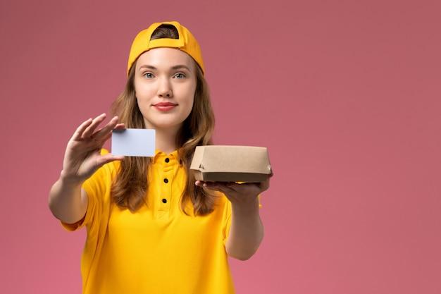 Вид спереди курьер-женщина в желтой форме и накидке с небольшим пакетом еды для доставки и пластиковой картой на розовой стене