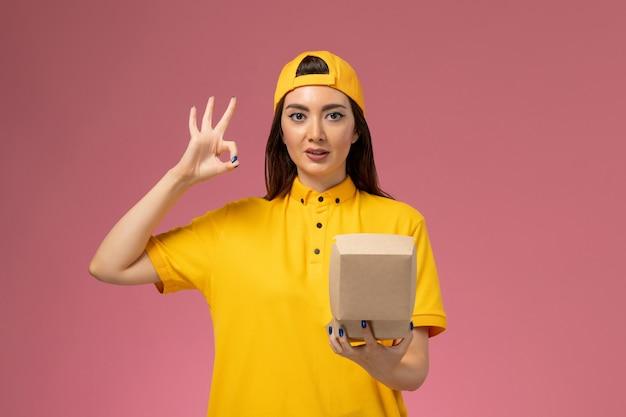 黄色の制服を着た正面図の女性宅配便と淡いピンクの壁に小さな配達食品パッケージを保持している岬サービス制服配達会社の仕事