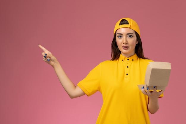 黄色の制服とケープの正面図の女性の宅配便は、淡いピンクの壁のサービスの制服配達会社の労働者に小さな配達食品パッケージを保持しています