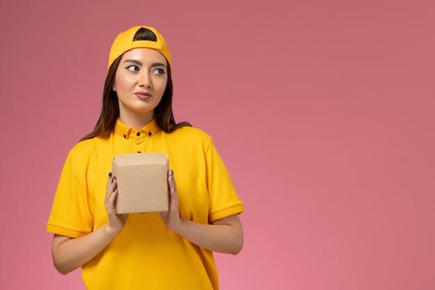 黄色の制服とケープの正面図の女性の宅配便は、淡いピンクの壁の制服の仕事サービスの配達会社に小さな配達食品パッケージを保持しています