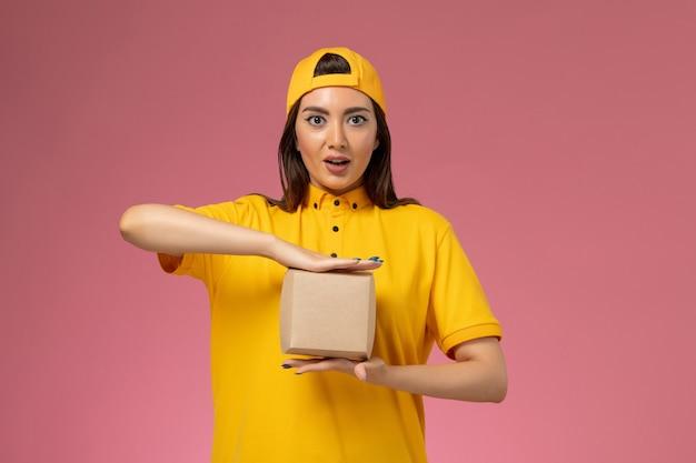 黄色のユニフォームと薄ピンクの壁に小さな配達食品パッケージを保持している岬の正面図の女性の宅配便制服サービス配達女の子の仕事会社