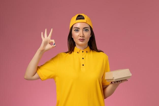 ピンクの壁の制服サービス配達会社の女の子に小さな配達食品パッケージを保持している黄色の制服と岬の正面図の女性の宅配便