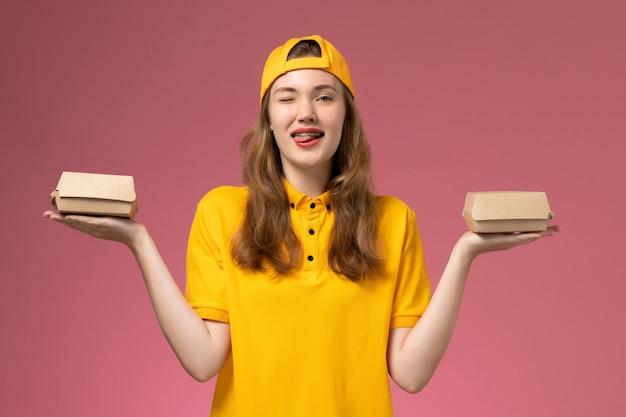 黄色の制服とケープの正面図の女性の宅配便は、淡いピンクの壁のサービスの仕事の配達の制服に小さな配達食品パッケージを保持しています