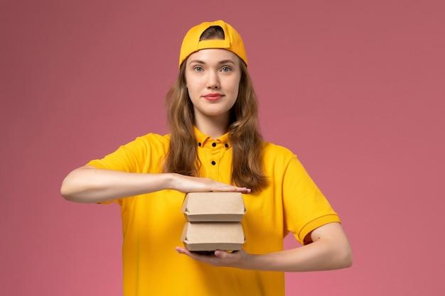 黄色の制服とピンクの壁に小さな配達食品パッケージを保持している岬の正面図の女性の宅配便サービス配達制服の仕事