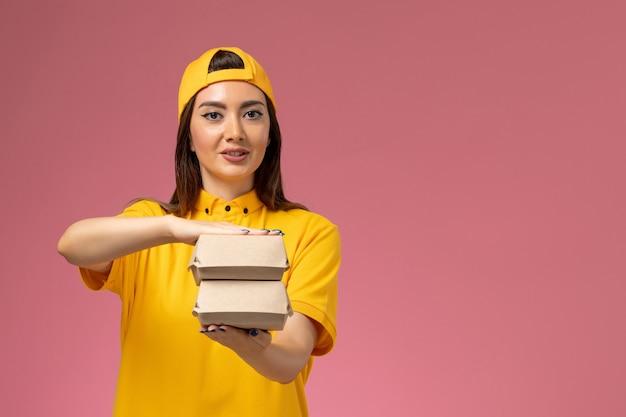 黄色の制服とケープの正面図の女性の宅配便は、淡いピンクの壁サービスの制服配達作業の仕事で小さな配達食品パッケージを保持しています