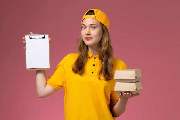 Вид спереди курьер-женщина в желтой форме и накидке с маленькими пакетами еды для доставки с блокнотом на розовой стене