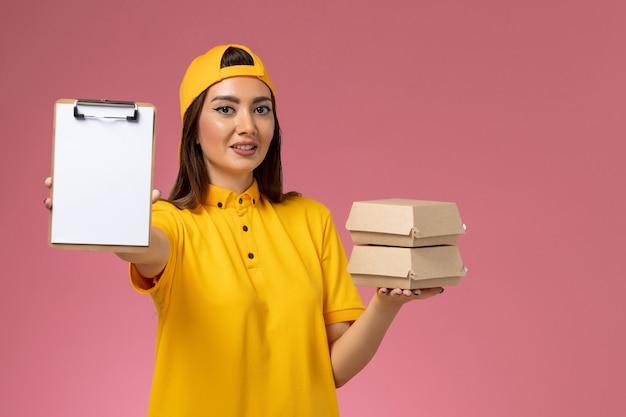 ピンクの壁のサービスの制服の配達の仕事にメモ帳で小さな配達食品パッケージを保持している黄色の制服と岬の正面図の女性の宅配便