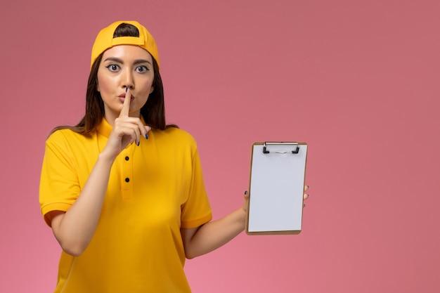 ピンクの机の会社のサービスの制服の配達にメモ帳を保持している黄色の制服とケープの正面図の女性の宅配便