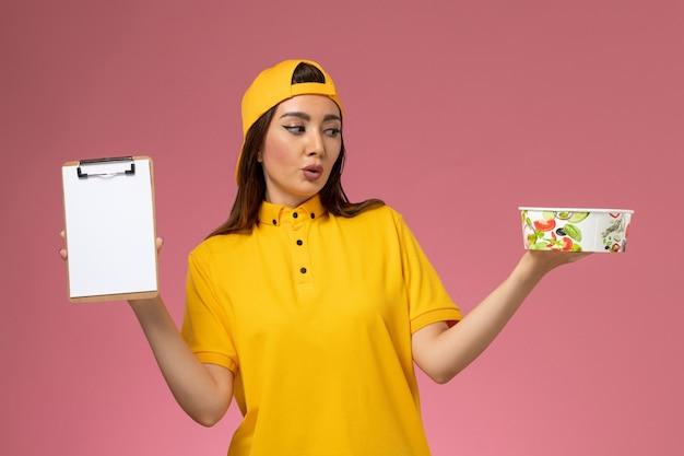 노란색 유니폼과 케이프 핑크 벽 서비스 유니폼 배달 소녀 노동자에 메모장 라운드 배달 그릇을 들고 전면보기 여성 택배