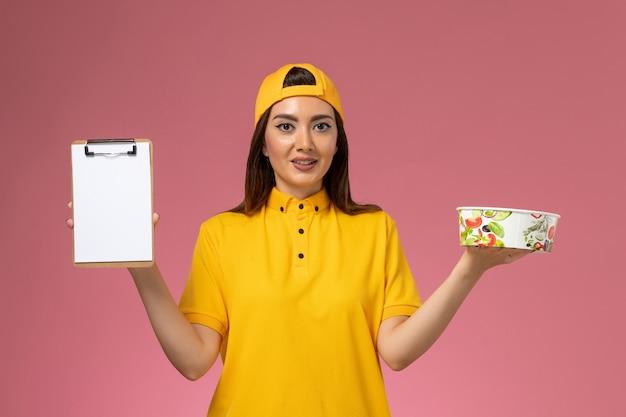 Вид спереди курьер-женщина в желтой форме и накидке держит круглую миску для доставки с блокнотом на розовой стене.