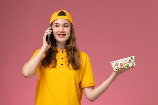 ピンクの壁の会社のサービスの仕事の配達の制服で電話を介して話している配達ボウルを保持している黄色の制服の正面図女性宅配便