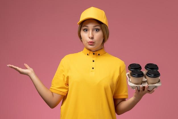 Вид спереди женщина-курьер в желтой форме с желтым плащом держит коричневые пластиковые кофейные чашки на розовом фоне.