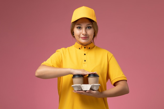 ピンクの背景に茶色のプラスチック製のコーヒーカップを保持している黄色の制服黄色のケープの正面図女性宅配便制服配達作業色の仕事