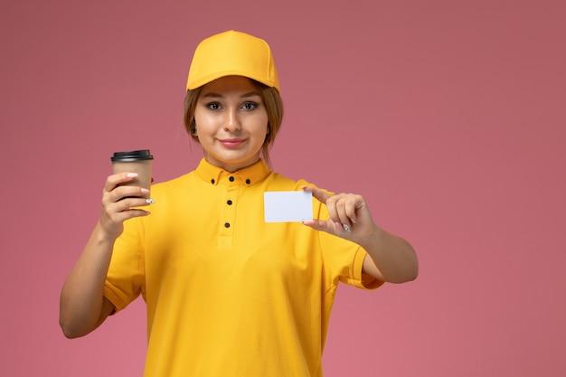 ピンクの机の上にコーヒーとカードを保持している黄色の制服黄色のケープの正面図女性宅配便制服仕事配達女性の色