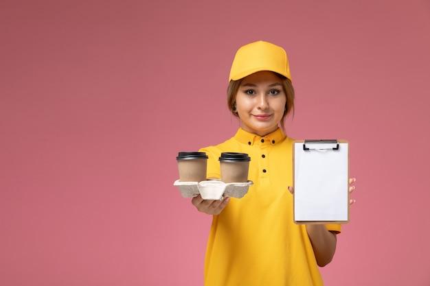 ピンクの背景の均一な配達の仕事でコーヒーとメモ帳を保持している黄色の制服黄色の岬の正面図の女性の宅配便