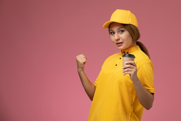 Вид спереди женщина-курьер в желтой униформе, желтой накидке, держащей чашку кофе на розовом столе, униформа доставщика работы