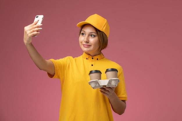 コーヒーカップを保持し、ピンクの背景に自分撮りをしている黄色の制服黄色の岬の正面図女性宅配便制服配達作業色の仕事