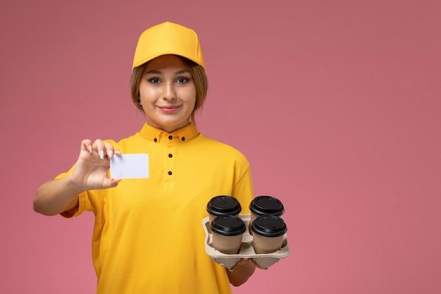 Вид спереди женщина-курьер в желтой униформе с желтым плащом держит кофейные чашки и белую карточку на розовом фоне.