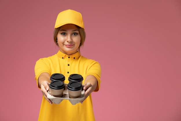 Вид спереди женщина-курьер в желтой униформе, желтой накидке с кофейными чашками на розовом фоне.