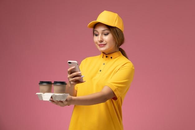 Вид спереди женщина-курьер в желтой униформе с желтым плащом держит кофейные чашки по телефону на розовом фоне.