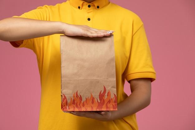 ピンクの背景に配達パッケージを保持している黄色の制服黄色の岬の正面図女性宅配便制服配達仕事の仕事
