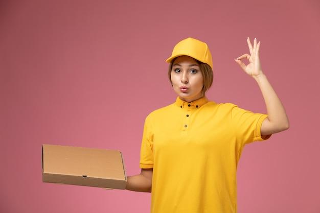ピンクの机の上のフードボックスパッケージを保持している黄色のユニフォーム黄色のケープの正面図女性の宅配便ユニフォーム配達女性の仕事の色