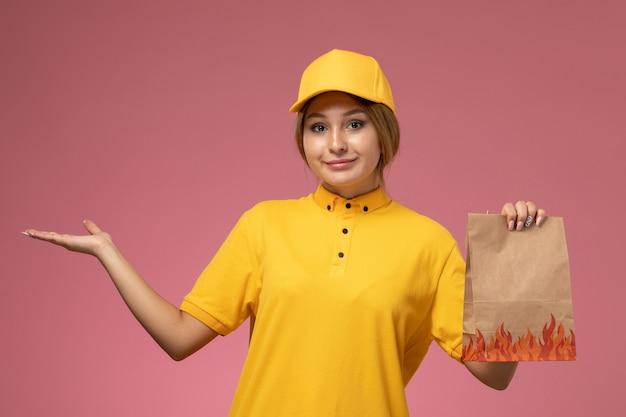 Вид спереди женщина-курьер в желтой униформе желтого плаща держит пакет с едой на розовом фоне.
