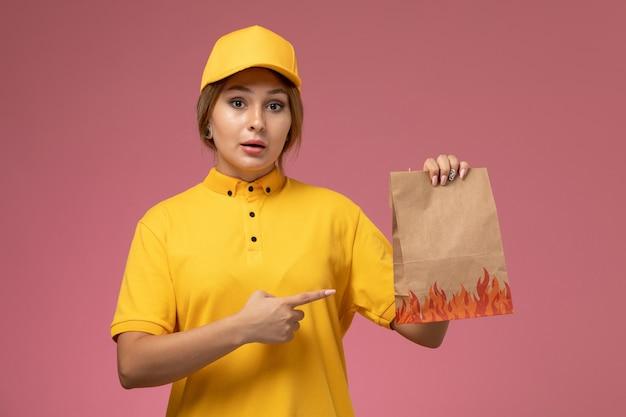 ピンクの背景に食品パッケージを保持している黄色の制服黄色のケープの正面図の女性の宅配便