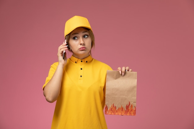 ピンクの背景の制服配達作業色の仕事で電話で話している食品パッケージを保持している黄色の制服黄色の岬の正面図女性宅配便