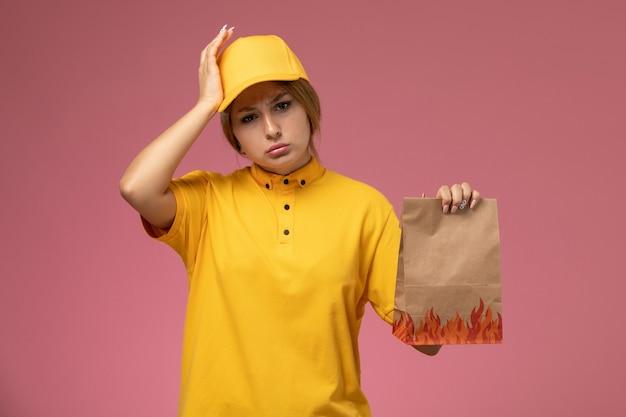 深刻な頭痛のピンクの背景の均一な配達作業色の仕事で食品パッケージを保持している黄色の制服黄色の岬の正面図の女性の宅配便