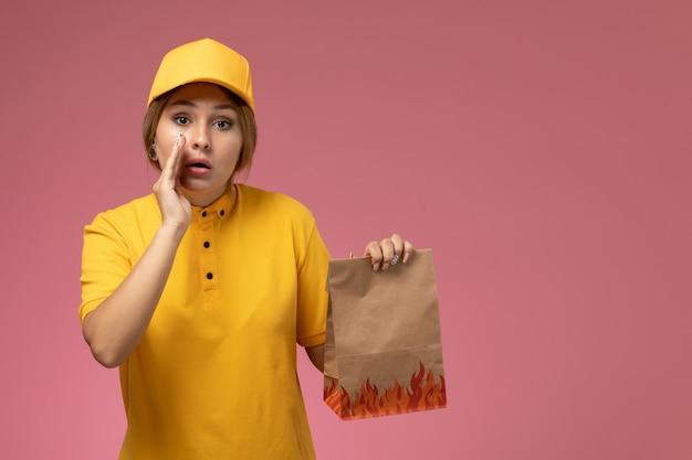 ピンクの背景の制服配達作業の仕事でささやく小さな食品パッケージを保持している黄色の制服黄色の岬の正面図の女性の宅配便