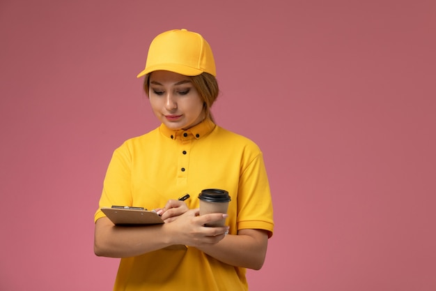 Вид спереди женщина-курьер в желтой форме с желтым плащом держит блокнот и чашку кофе на розовом фоне.