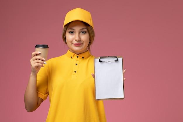 Вид спереди женщина-курьер в желтой униформе, желтой накидке, держащей блокнот пластиковую чашку кофе на розовом фоне.