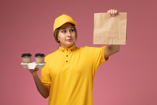 Вид спереди женщина-курьер в желтой форме, желтая накидка, держащая пластиковые коричневые кофейные чашки, пакет продуктов на розовом столе, доставка униформы, цвет девушки